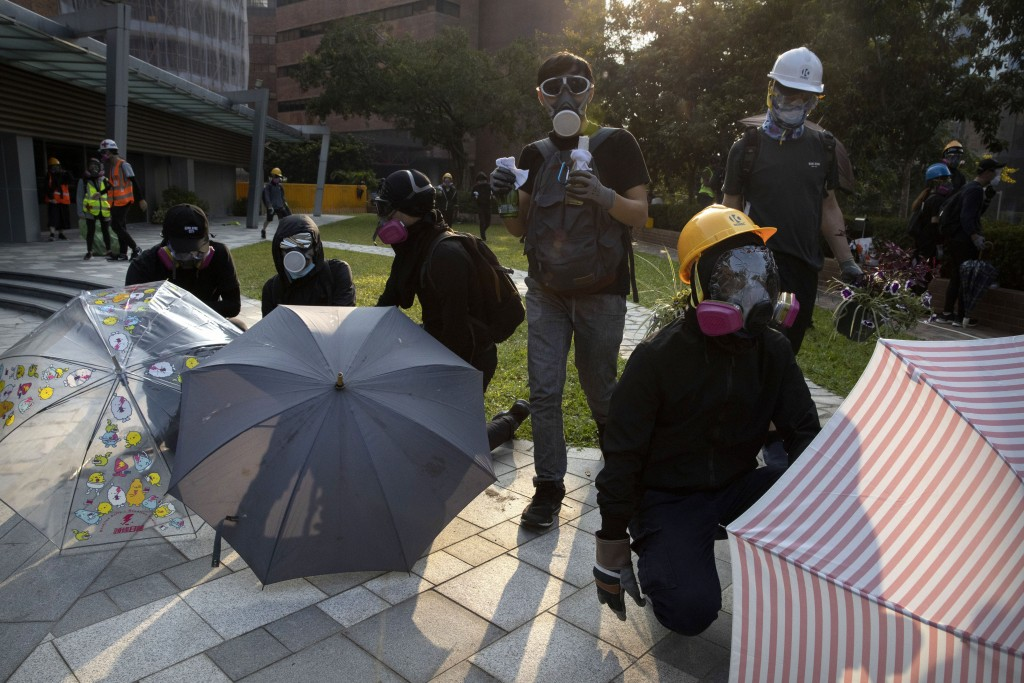 A protestor carrying molotov cocktails stands with others holding umbrellas as they wait for a possible volley of tear gas at the Hong Kong Polytechni...