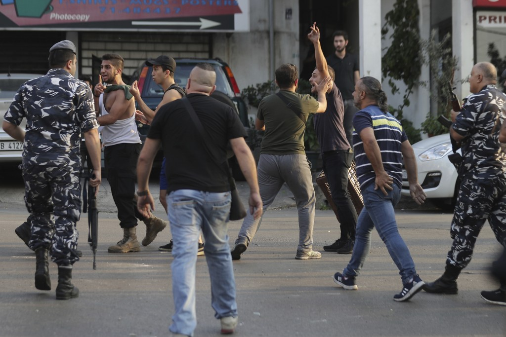 Angry anti-Government protesters scuffle with Lebanese policemen after a supporter of President Michel Aoun opened fire over the heads of protesters i...