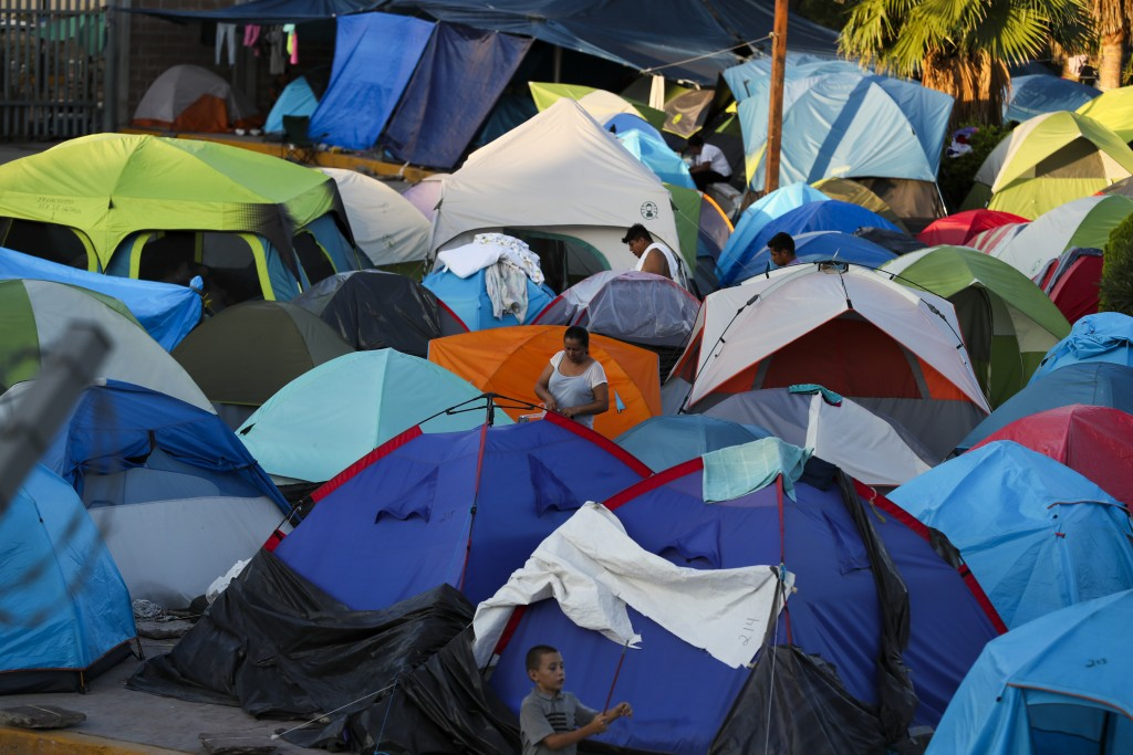 ADVANCE FOR USE SUNDAY, NOV. 17, 2019 AND THEREAFTER- In this Oct. 11, 2019 photo, migrants wake up at a camp set up by migrants waiting near a legal ...