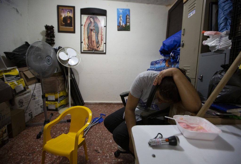 ADVANCE FOR USE SUNDAY, NOV. 17, 2019 AND THEREAFTER- In this Sept. 18, 2019 photo, Linda, the wife of Nicaraguan migrant Yohan leans over a cell phon...