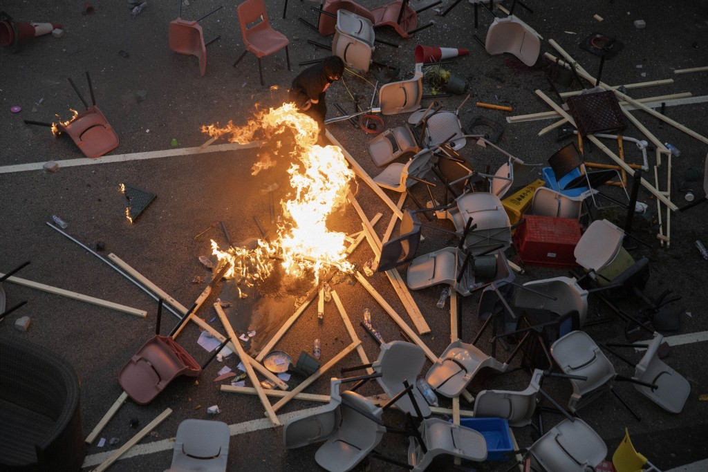 A protester tries to pour water on a fire burning amid debris placed to block a road leading to the Cross-Harbour Tunnel in Hong Kong, Thursday, Nov. ...