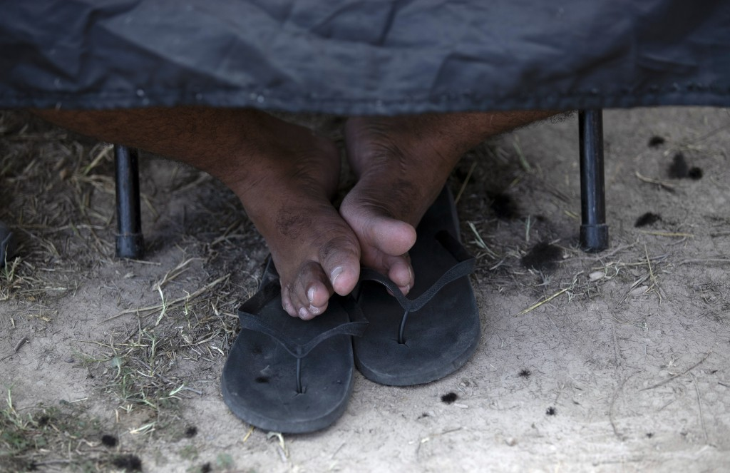 ADVANCE FOR USE SUNDAY, NOV. 17, 2019 AND THEREAFTER- In this Oct. 11, 2019 photo, the feet of a migrant boy rest on his sandals as he sits still for ...