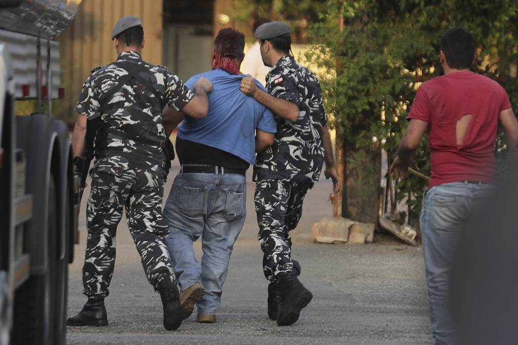 Policemen arrest a supporter of President Michel Aoun, center, who opened fire over the heads of protesters in the town of Jal el-Dib, north of Beirut...