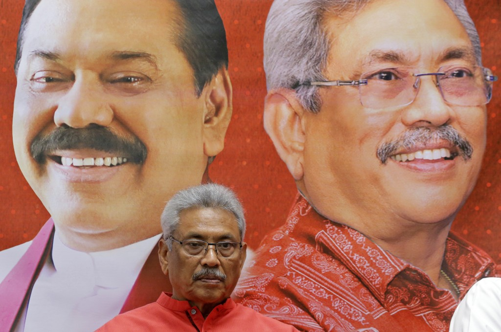 In this Nov. 6, 2019 photo, Sri Lankan presidential candidate and former defense chief Gotabaya Rajapaksa is seated next to a billboard carrying portr...
