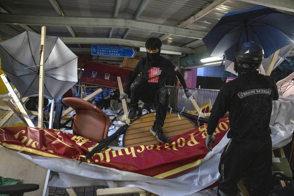 Protesters climb over a barricade on an overhead bridge near the Cross-Harbour Tunnel in Hong Kong, Thursday, Nov. 14, 2019. University students from ...