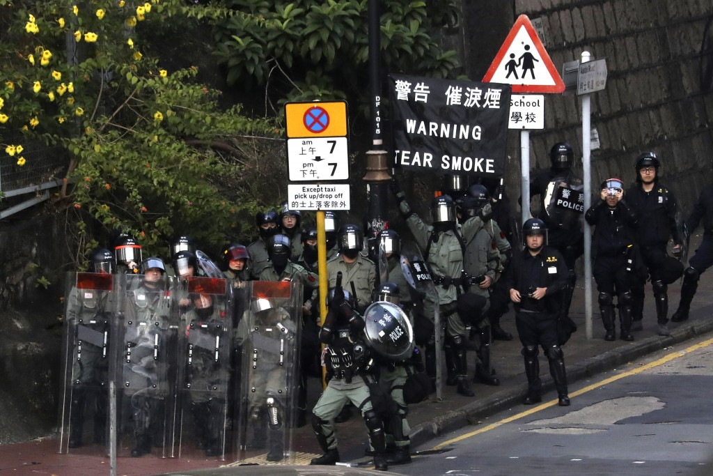 A riot police, center, aims his tear gas gun during a face-off with pro-democracy protesters at the campus of the Hong Kong Polytechnic University, in...