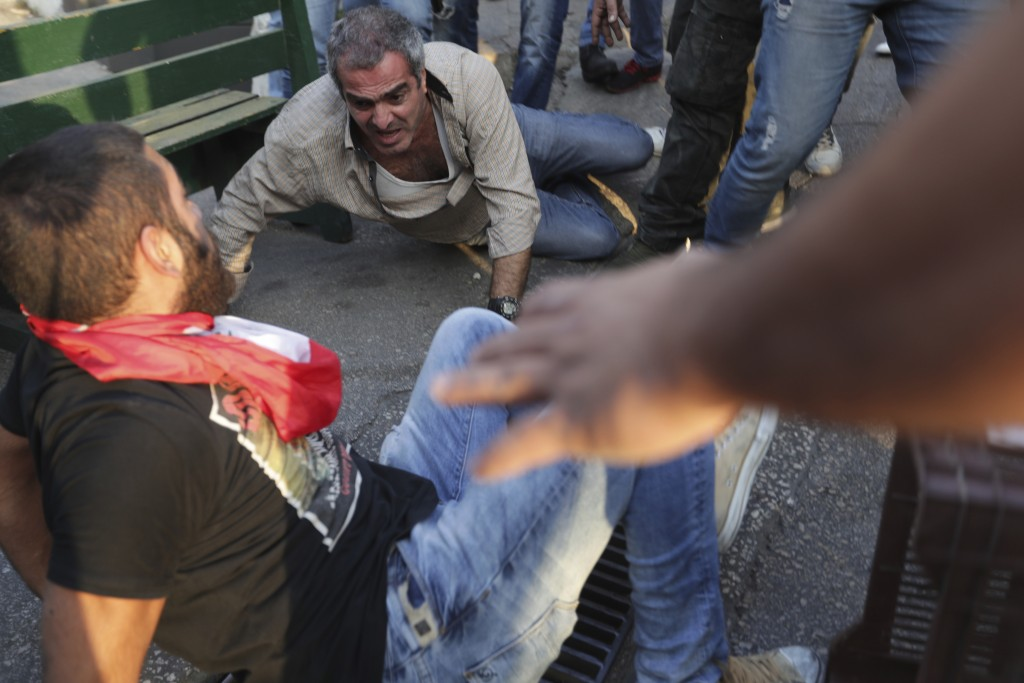 Protesters attack a supporter of President Michel Aoun, center, after they found an automatic rifle used in a shooting in his car, in the town of Jal ...