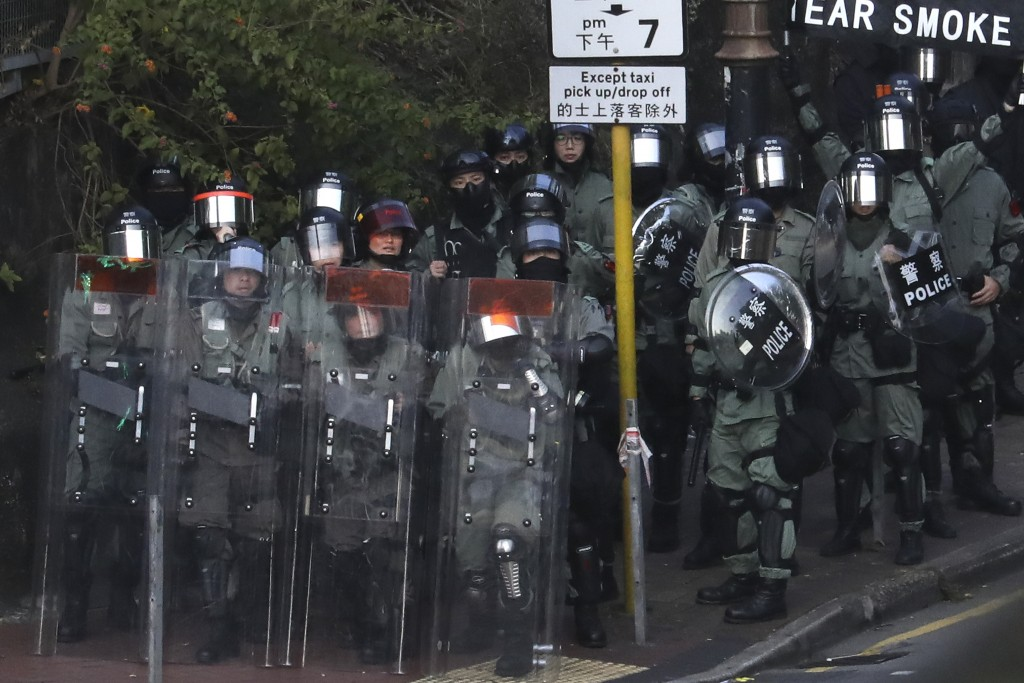 Riot police stand guard as they face off with pro-democracy protesters at the campus of the Hong Kong Polytechnic University, in Hong Kong, Thursday, ...