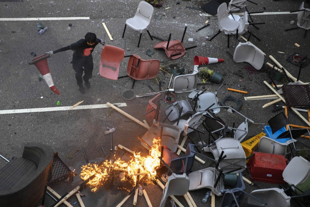 A protester tries remove plastic items from a fire burning amid debris placed to block a road leading to the Cross-Harbour Tunnel in Hong Kong, Thursd...
