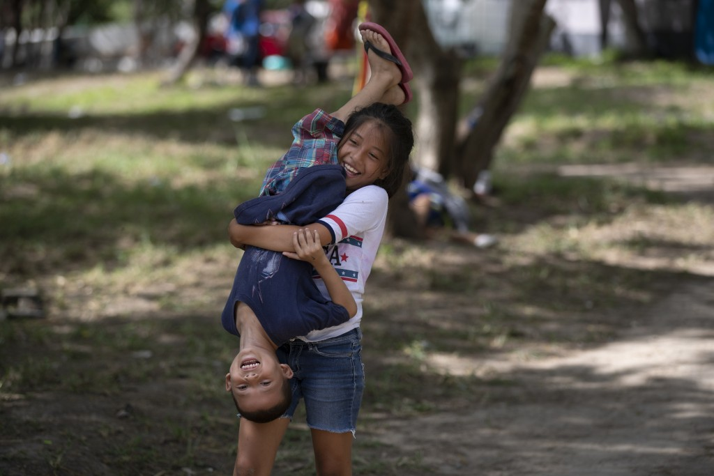 ADVANCE FOR USE SUNDAY, NOV. 17, 2019 AND THEREAFTER- In this Oct. 11, 2019 photo, migrant children play in an area where other migrants set up camp n...