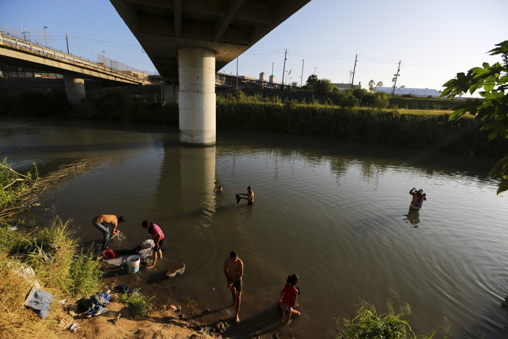 ADVANCE FOR USE SUNDAY, NOV. 17, 2019 AND THEREAFTER- In this Oct. 11, 2019 photo, migrants wash their clothes in the Rio Grande in Matamoros, Mexico,...