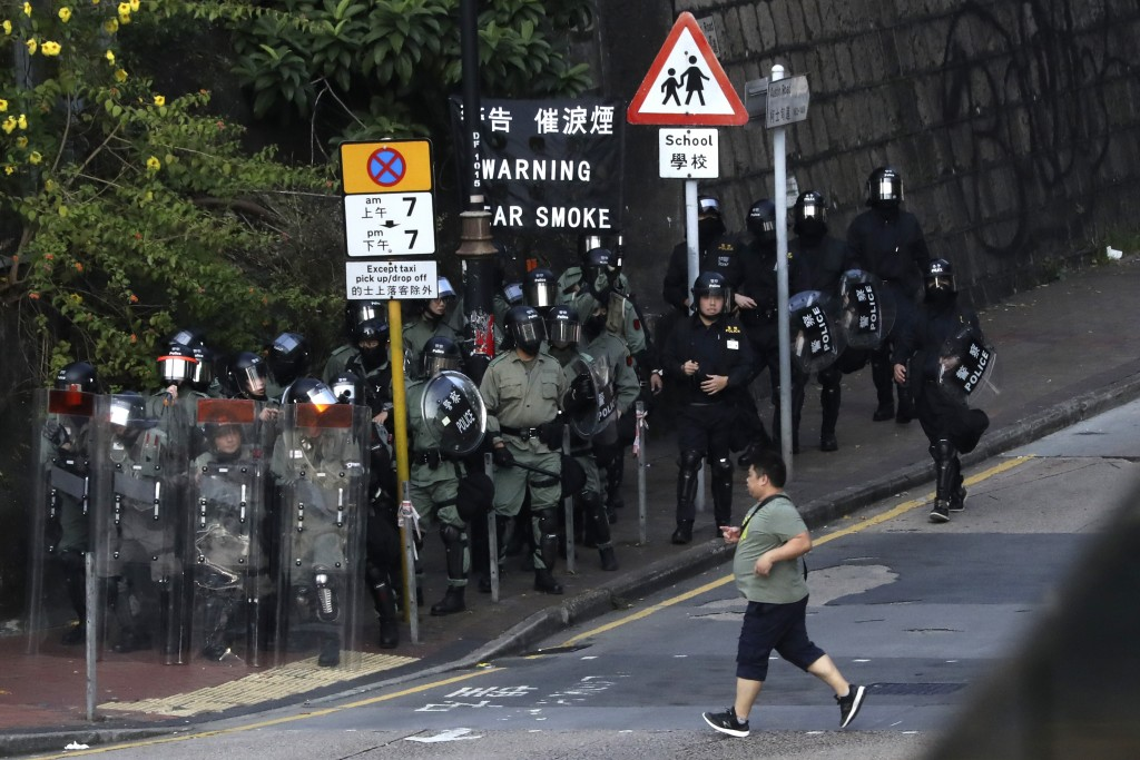 A man runs past riot policemen gathering near the campus of the Hong Kong Polytechnic University as they face-off with pro-democracy protesters in Hon...