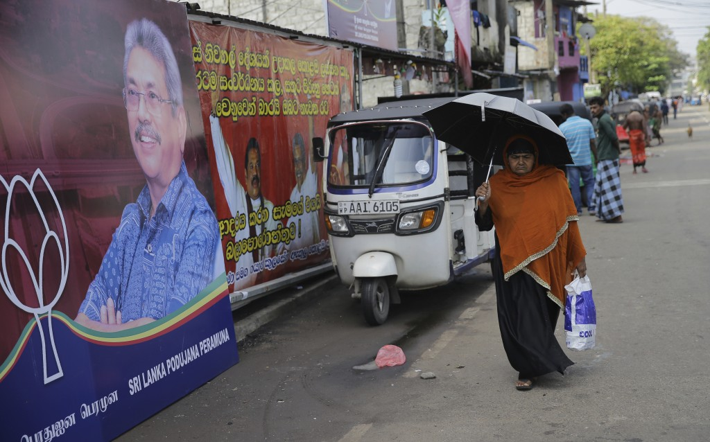 In this Wednesday, Nov. 13, 2019 photo, a Sri Lankan woman walks past election propaganda of presidential candidate and former defense chief Gotabaya ...