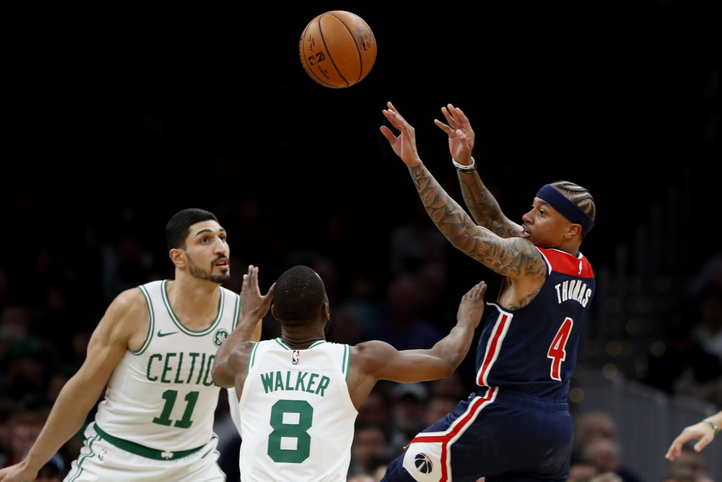 Washington Wizards' Isaiah Thomas passes the ball over Boston Celtics' Kemba Walker and Enes Kanter (11) during the first quarter of an NBA basketball...
