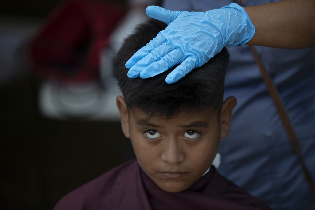 ADVANCE FOR USE SUNDAY, NOV. 17, 2019 AND THEREAFTER- In this Oct. 11, 2019 photo, a young migrant gets a free haircut by a volunteer at a migrant cam...