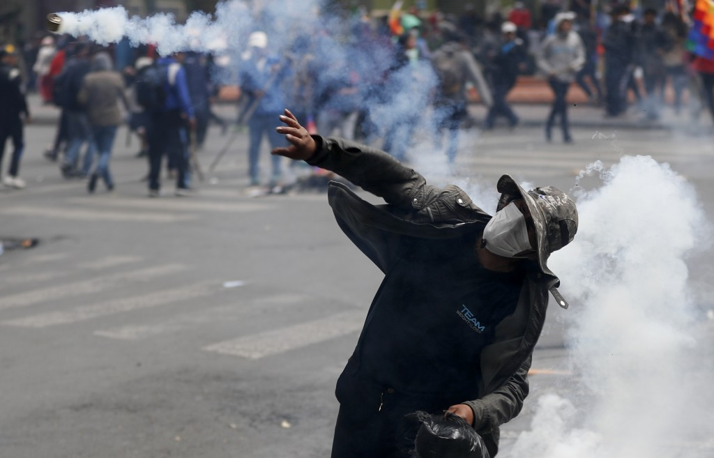 A backer of former President Evo Morales throws back a tear gas canister at police during clashes in La Paz, Bolivia, Wednesday, Nov. 13, 2019. Bolivi...
