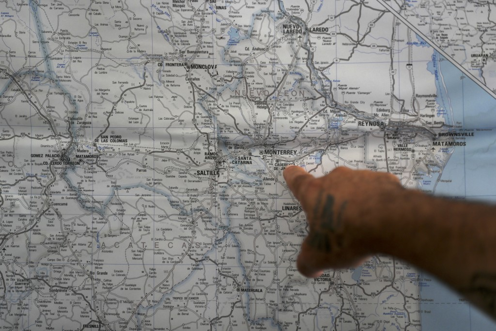 ADVANCE FOR USE SUNDAY, NOV. 17, 2019 AND THEREAFTER- In this Oct. 10, 2019 photo, a Mexican migrant points to a map of U.S.-Mexico border cities, han...