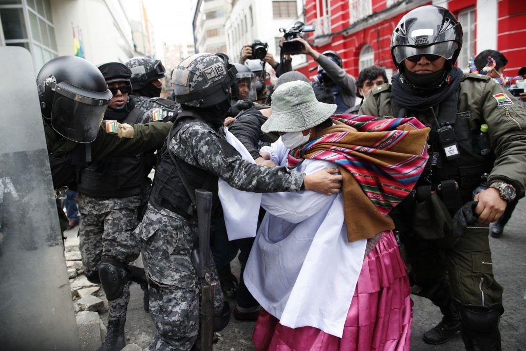 A backer of former President Evo Morales scuffles with police in La Paz, Bolivia, Wednesday, Nov. 13, 2019. The opposition senator who has claimed Bol...