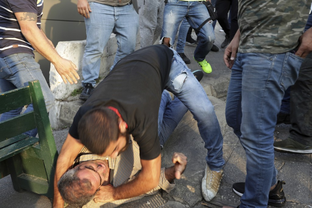 Protesters hold down a supporter of President Michel Aoun, after they found an automatic rifle used in a shooting in his car, in the town of Jal el-Di...