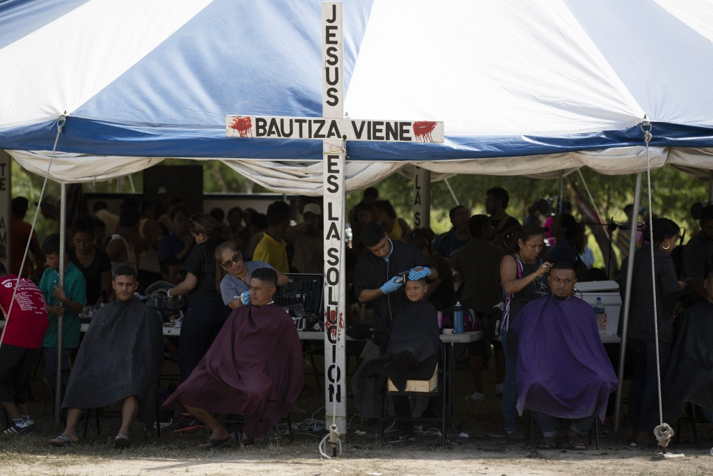 ADVANCE FOR USE SUNDAY, NOV. 17, 2019 AND THEREAFTER- In this Oct. 11, 2019 photo, migrants get free haircuts by volunteers at a migrant camp near a l...