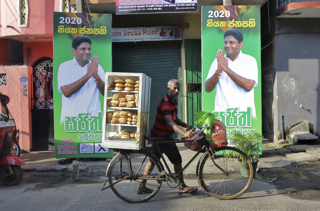 In this Wednesday, Nov. 13, 2019 photo, a Sri Lankan bread vendor pushes his bicycle past election propaganda of presidential candidate representing t...