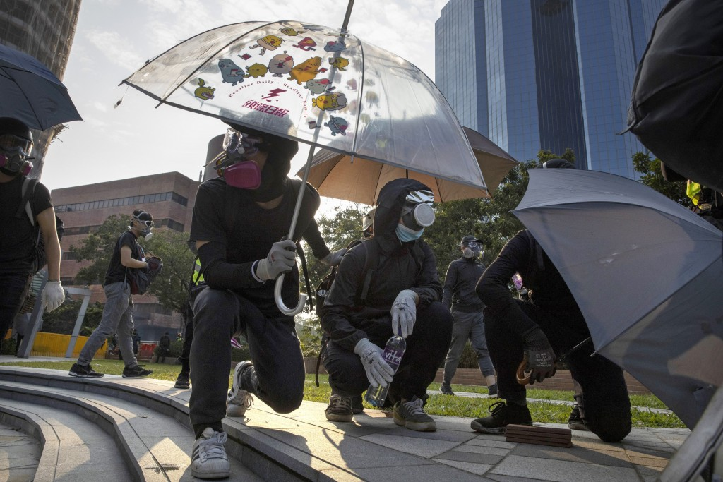 Protestors hold umbrellas as they wait for a possible volley of tear gas at the Hong Kong Polytechnic University campus in Hong Kong, Thursday, Nov. 1...