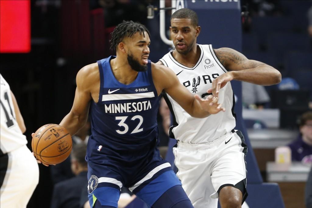 Minnesota Timberwolves' Karl-Anthony Towns, left, drives around San Antonio Spurs' LaMarcus Aldridge in the first half of an NBA basketball game Wedne...