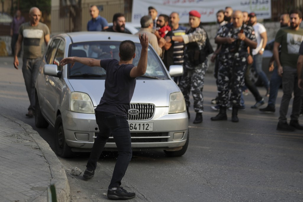 Anti-Government protesters throw stones at the car belonging to a supporter of President Michel Aoun, with whom they found an automatic rifle used in ...