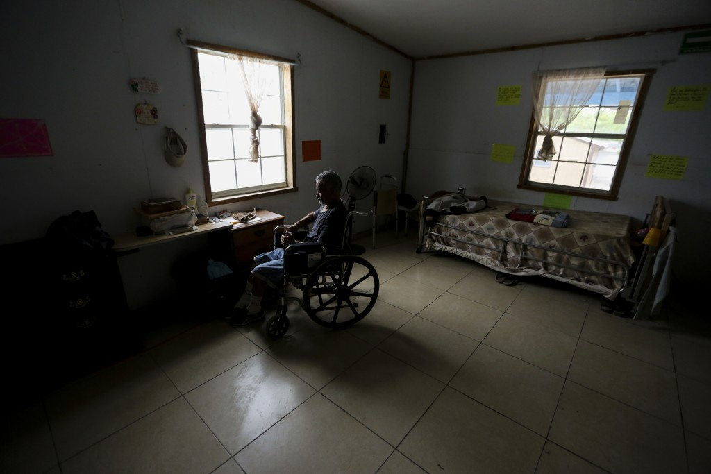 ADVANCE FOR USE SUNDAY, NOV. 17, 2019 AND THEREAFTER-In this Oct. 12, 2019 photo, a Cuban migrant who applied for asylum in the U.S. sits in a wheelch...