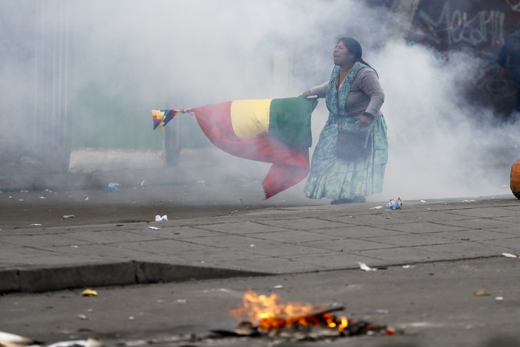 A supporter of former President Evo Morales holds a Bolivian flag during clashes with police in La Paz, Bolivia, Wednesday, Nov. 13, 2019. Bolivia's n...
