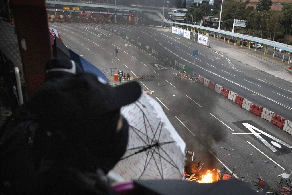 A protester watches as a fire burns amid debris placed to block a road leading to the Cross-Harbour Tunnel in Hong Kong, Thursday, Nov. 14, 2019. Univ...
