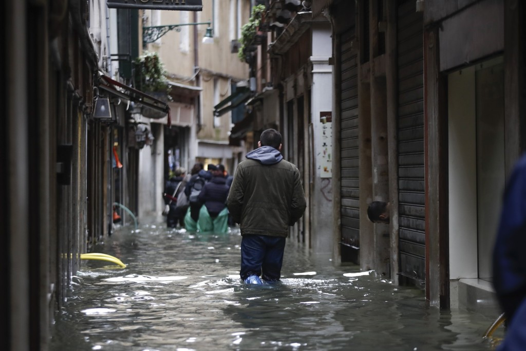 People wade their way through water in Venice, Italy, Friday, Nov. 15, 2019. Waters are rising in Venice where the tide is reaching exceptional levels...
