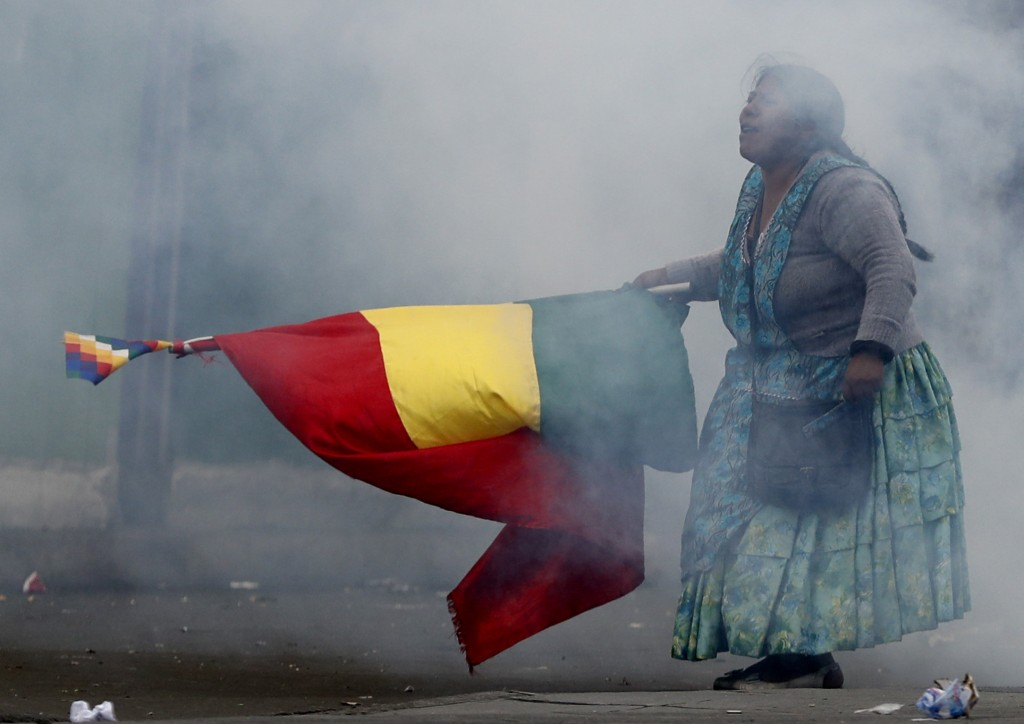 In this Wednesday, Nov. 13, 2019 photo, a supporter of former President Evo Morales holds a Bolivian flag during clashes with police in La Paz, Bolivi...