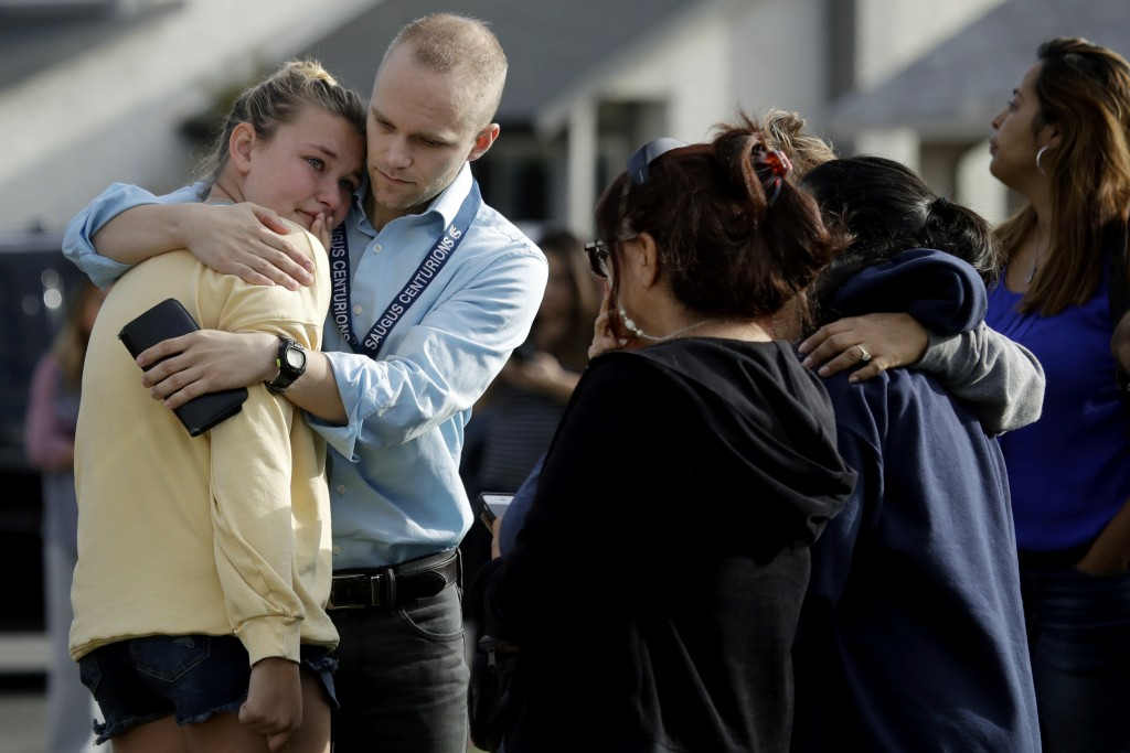 D.J. Hamburger, center in blue, a teacher at Saugus High School, comforts a student after reports of a shooting at the school on Thursday, Nov. 14, 20...