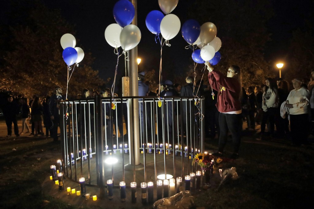 Jessica Dumont, a former student at Saugus High School, places balloons on a makeshift memorial at Central Park in honor of the victims of a shooting ...