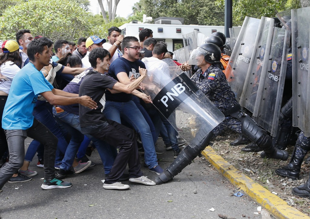 In this Thursday, Nov. 14, 2019 photo, university students try to take away the shield from a member of the National Bolivarian Police during clashes ...