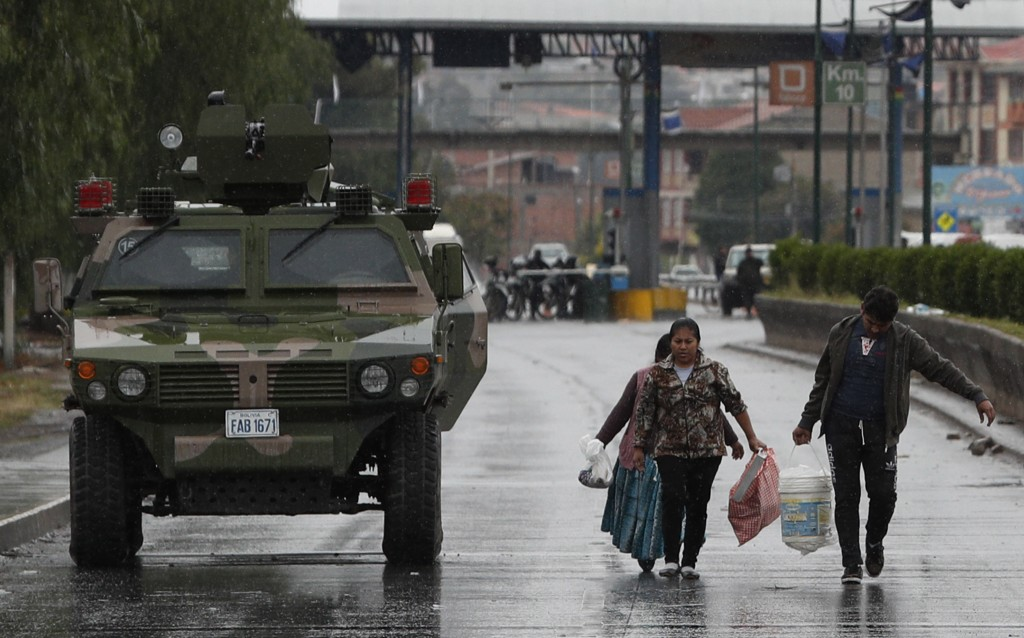 People walk past a military armored vehicle patrolling in Sacaba, Bolivia, Thursday, Nov. 14, 2019. Bolivia's former President Evo Morales resigned an...