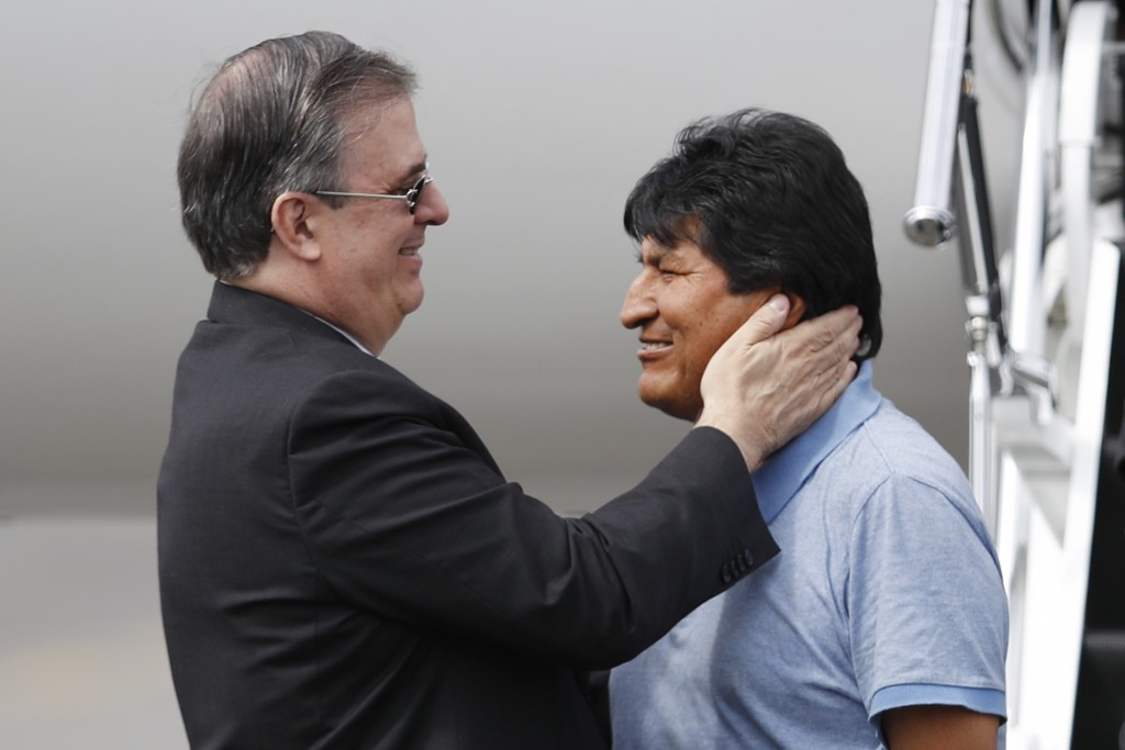 In this Tuesday, Nov. 12, 2019 photo, Mexican Foreign Minister Marcelo Ebrard, left, welcomes former Bolivian President Evo Morales upon his arrival t...