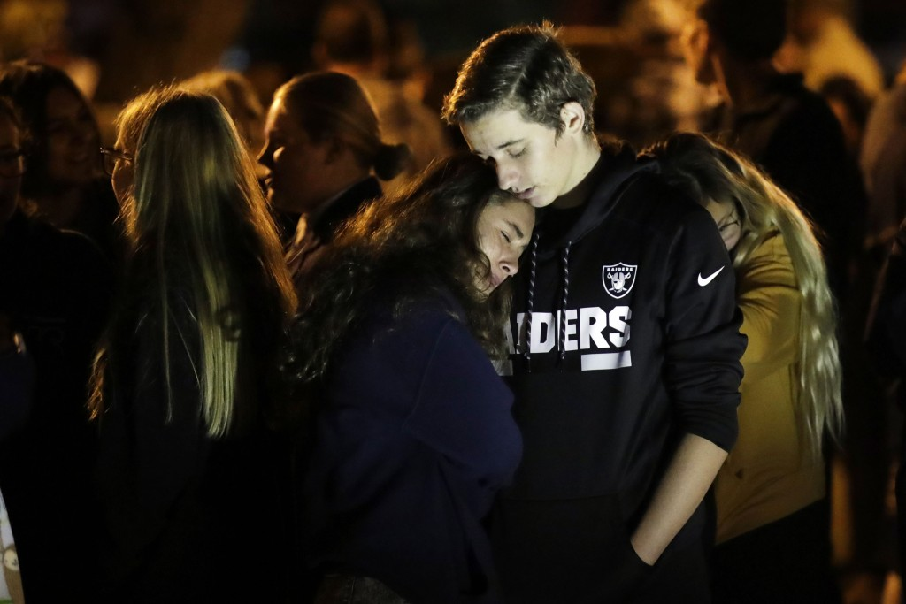 Hannah Schooping-Gutierrez, center, a student at Saugus High School, is comforted by her boyfriend Declan Sheridan, at right, a student at nearby Vale...