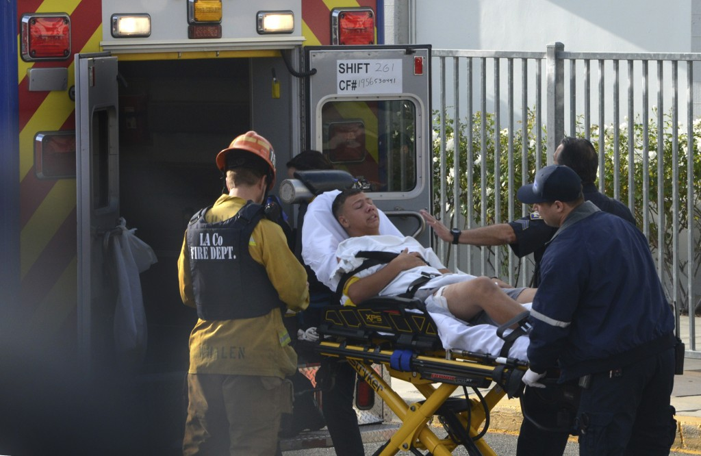 Medical personnel load an injured person into an ambulance outside Saugus High School in Santa Clarita, Calif., after a student gunman opened fire at ...