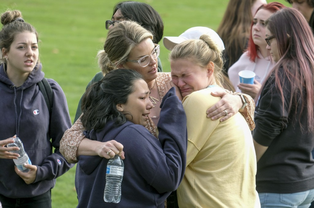 Students are comforted as they wait to be reunited with their parents following a shooting at Saugus High School that injured several people, Thursday...