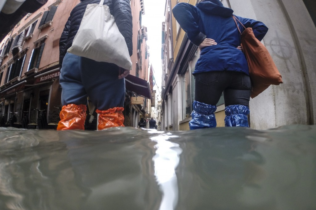 People wade their way through water in Venice, Italy, Friday, Nov. 15, 2019. Exceptionally high tidal waters returned to Venice on Friday, prompting t...