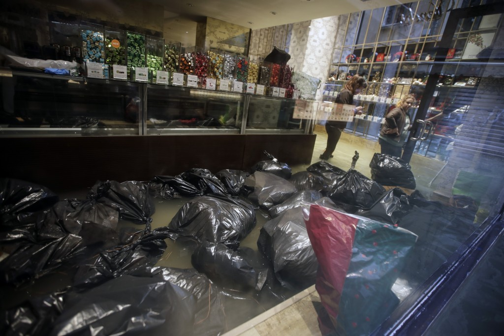 Garbage bags float inside a shop Venice, Italy, Friday, Nov. 15, 2019. Waters are rising in Venice where the tide is reaching exceptional levels just ...