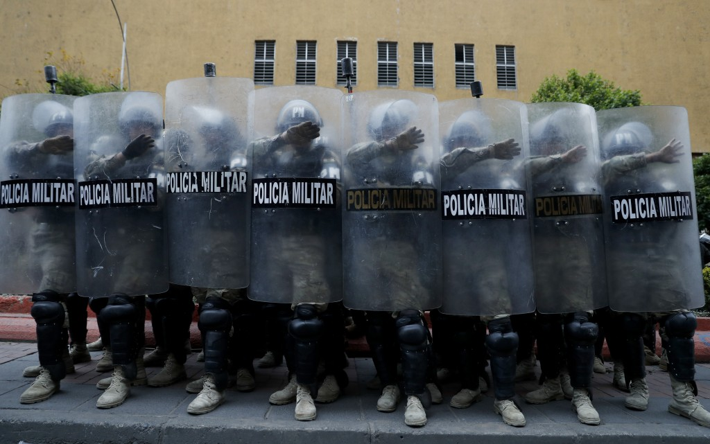 Military Police take cover behind their shields during a march of supporters of former President Evo Morales in La Paz, Bolivia, Thursday, Nov. 14, 20...
