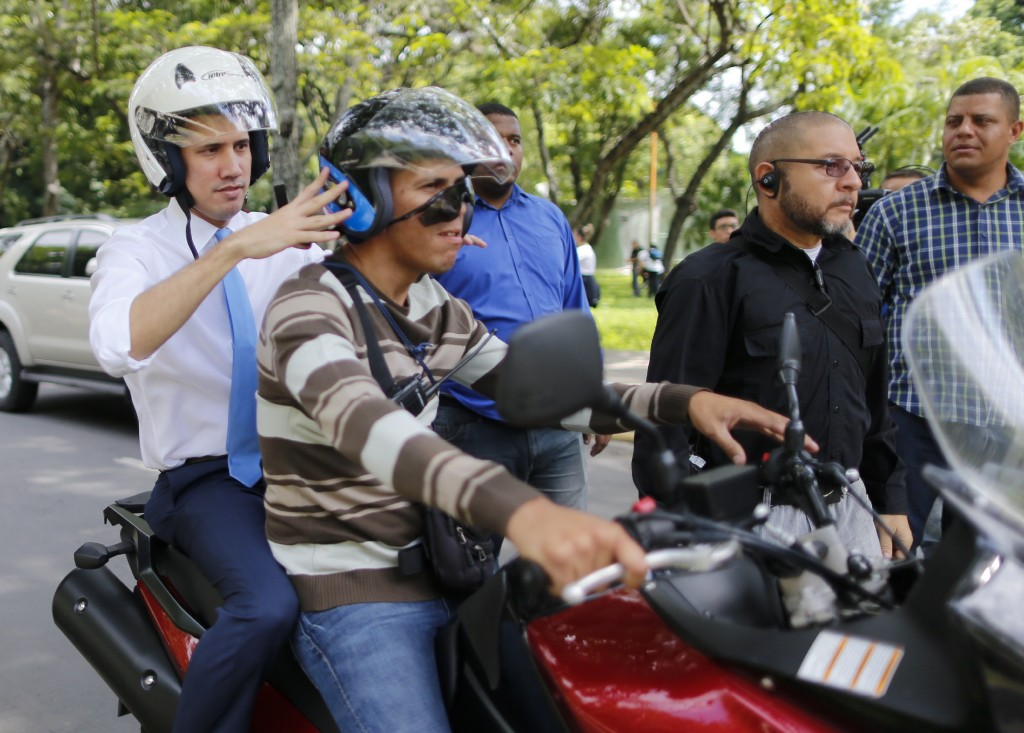 Juan Guaido, Venezuelan opposition leader, and self-proclaimed interim president of Venezuela, adjusts the helmet on a motorcycle driver as he is  dri...