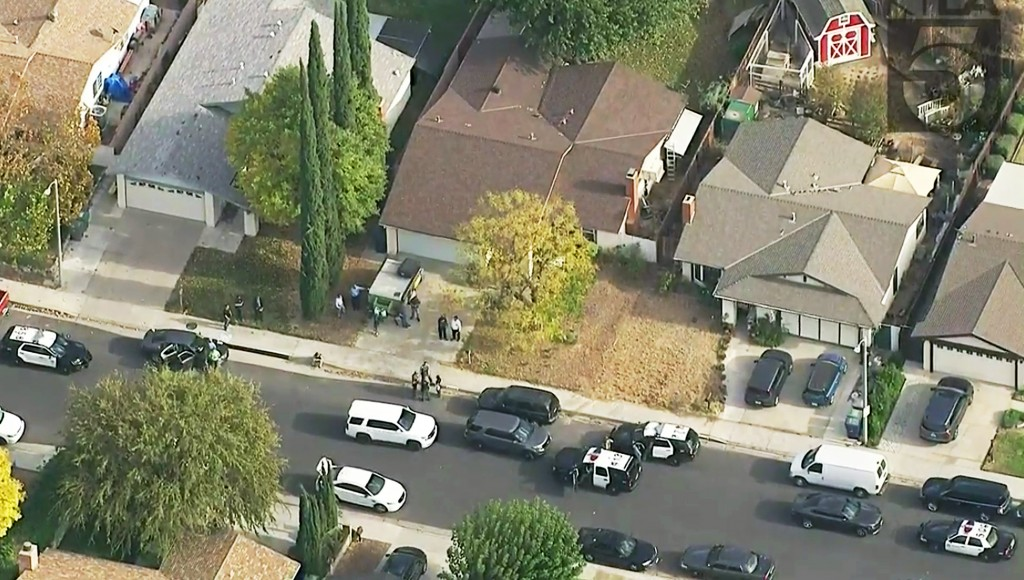 This photo from video provided by KTLA-TV shows police vehicles filling the street in front of the home of the alleged shooter, with the brown roof at...