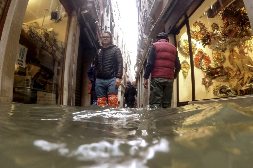 People make their way through water in Venice, Italy, Friday, Nov. 15, 2019. Exceptionally high tidal waters returned to Venice on Friday, prompting t...