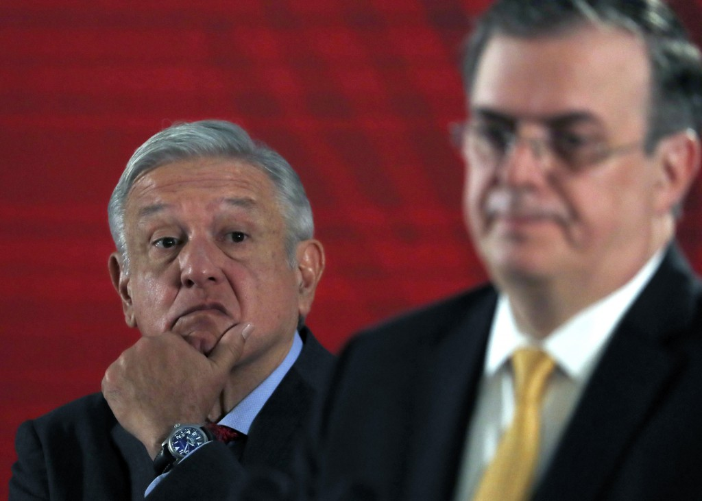 In this Tuesday, Nov. 12, 2019 photo, Mexican President Andres Manuel Lopez Obrador watches as his Foreign Minister, Marcelo Ebrard, answers questions...