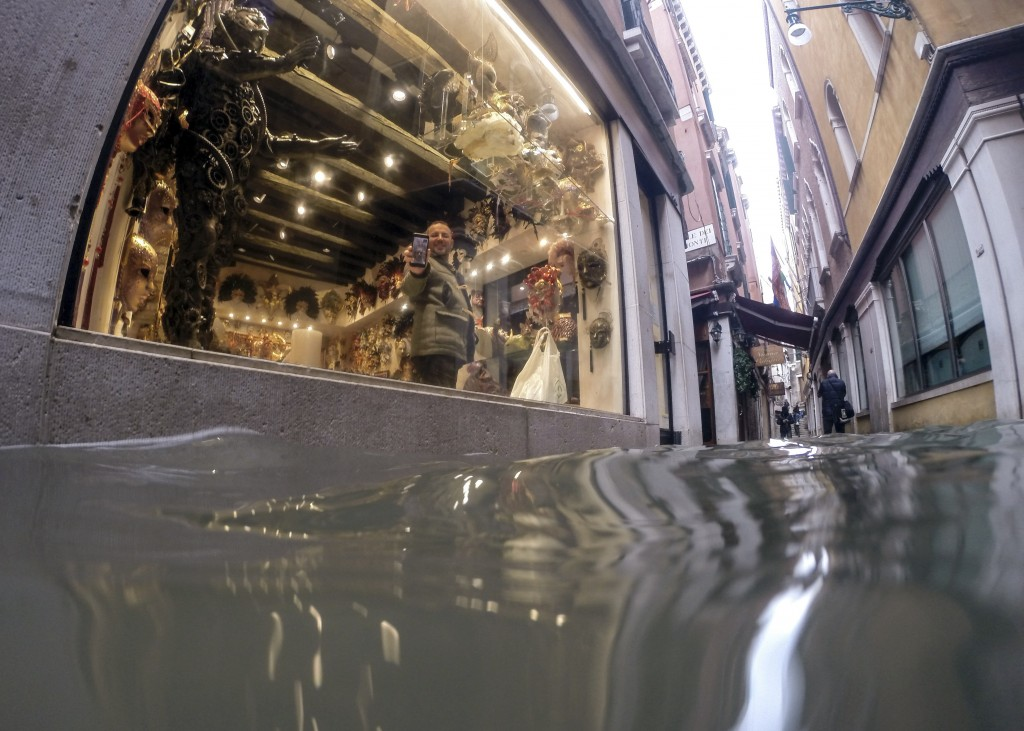 A man holds up a phone during a video call to show a a flooded alley outside a shop, in Venice, Italy, Friday, Nov. 15, 2019. Exceptionally high tidal...