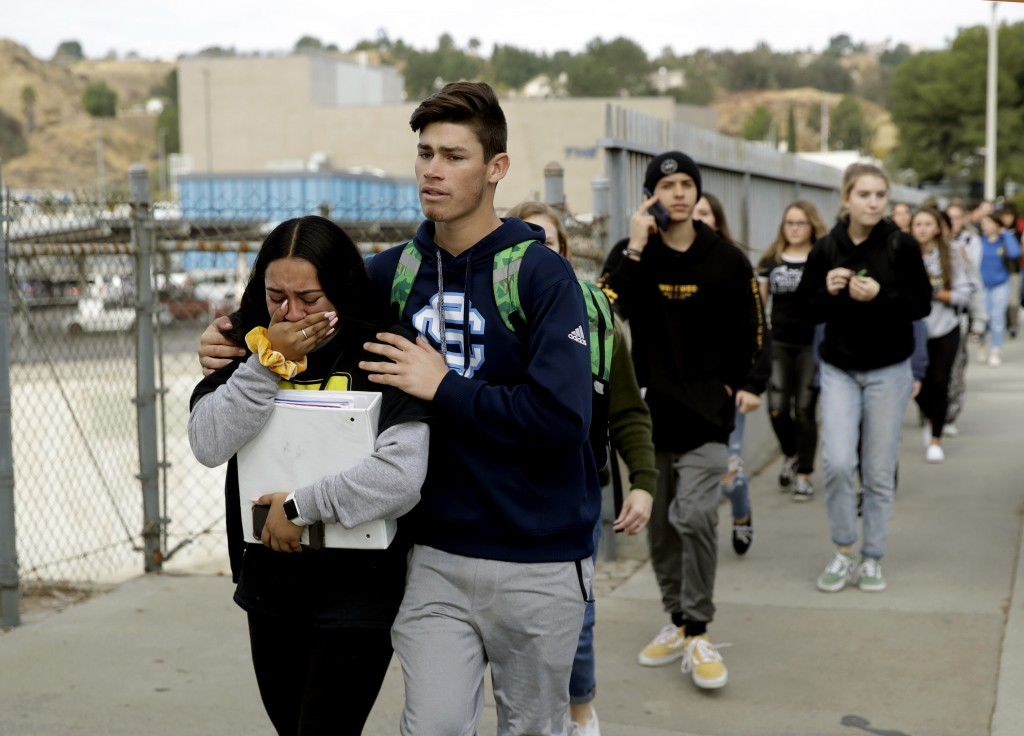 Students are escorted out of Saugus High School after reports of a shooting on Thursday, Nov. 14, 2019, in Santa Clarita, Calif. (AP Photo/Marcio Jose...